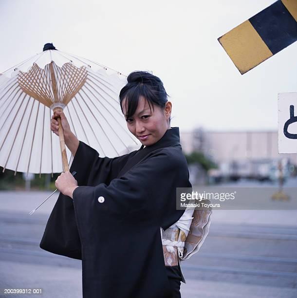 Woman wearing kimono holding parasol, smiling, portrait