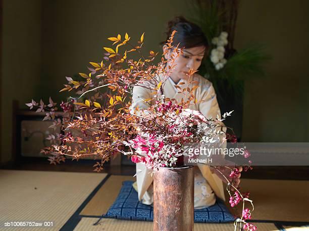 Woman wearing kimono kneeling down and arranging flowers