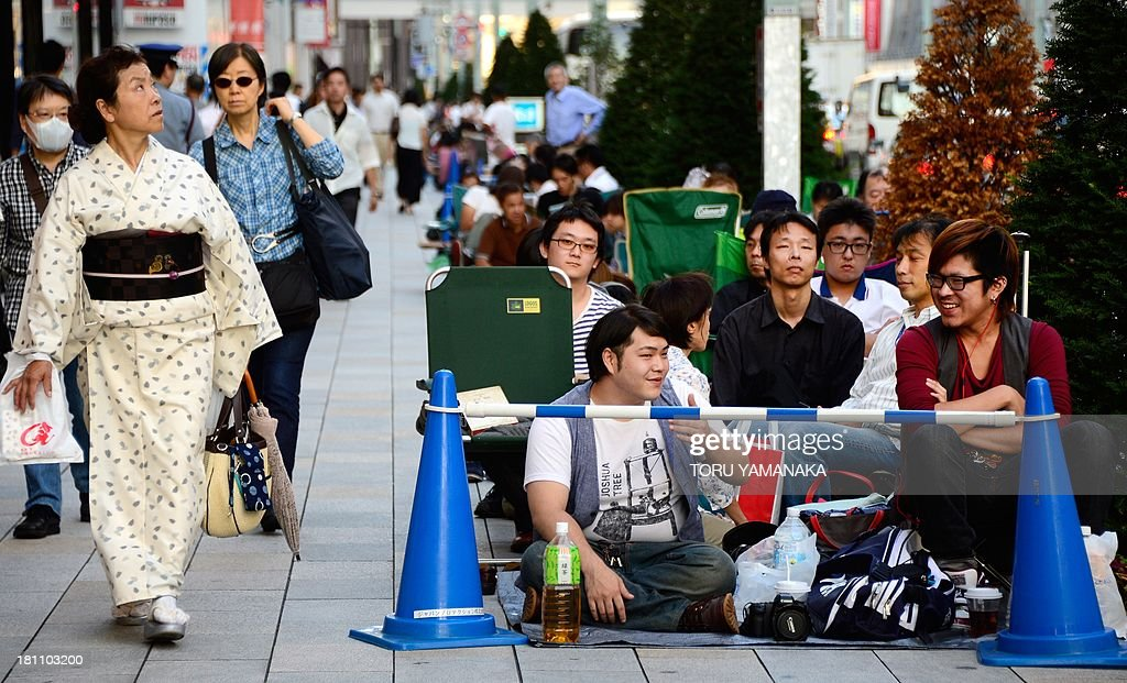 A woman wearing kimono (L) walks beside people sitting down as they queue in front of an Apple Store at Ginza shopping district to wait for the new iPhone 5s and 5c in Tokyo on September 19, 2013, a day before Apple's new smart phone will go on sale. The new iPhones go on sale on September 20. AFP PHOTO/Toru YAMANAKA