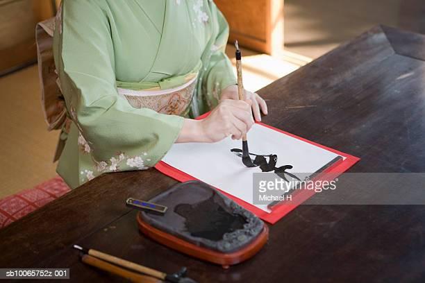 Woman wearing kimono writing calligraphy, mid section