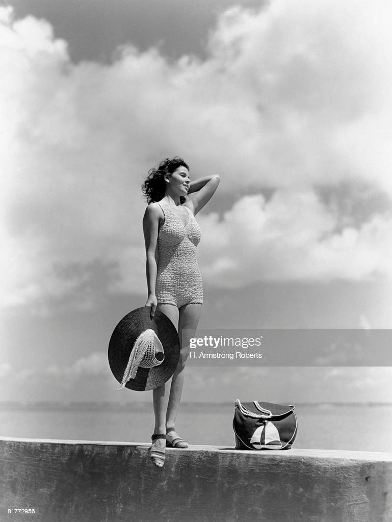 Woman Wearing Knit Bathing Suit Standing Wall Ocean Sea Background Holding Sun Hat Beach Bag Sail Boat Fashion Beauty Style Swim Wear Retro. : Stock Photo