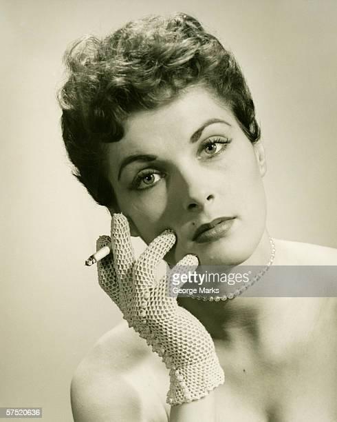 Woman wearing lace glove holding cigarette in studio, (B&W), portrait