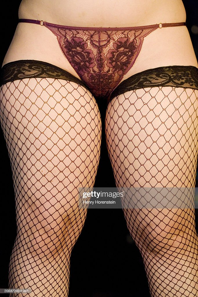 Woman wearing lace underwear and fishnet stockings, low section : Stock Photo