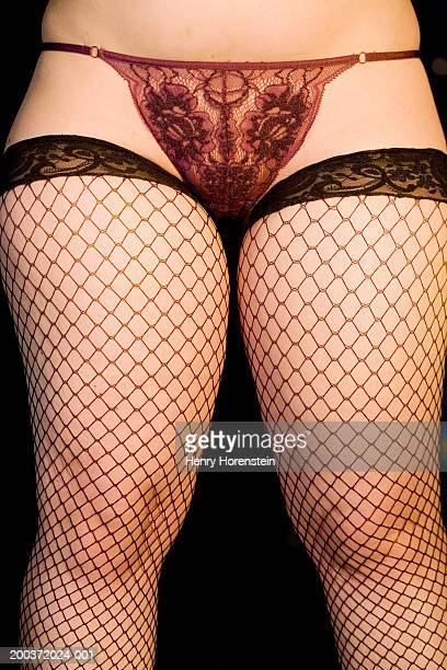Woman wearing lace underwear and fishnet stockings, low section