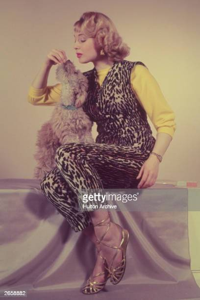 A woman wearing leopard print trousers and matching waistcoat playing with a poodle