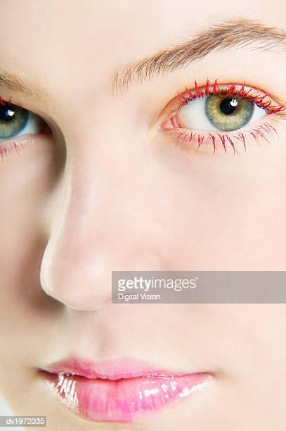 Woman Wearing Lip-gloss and Red Mascara