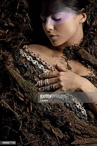 woman wearing luxury jewellery laying down in dirt
