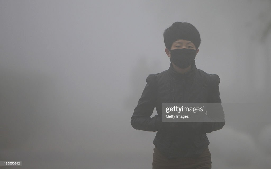 A woman wearing mask walks along a road as heavy smog engulfs the city on October 21 2013 in Changchun China Expressways schools and an airport...