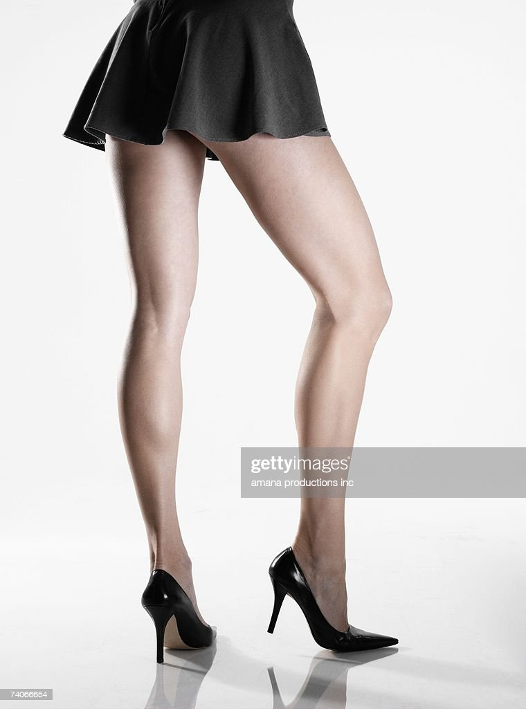 Woman wearing mini skirt and high heels (low section, rear view) : Stock Photo