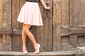 Woman wearing nude colored high heel shoes; fashion shoot in old city