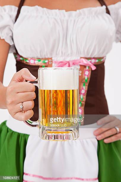 Woman wearing Oktoberfest costume holding a mug of beer