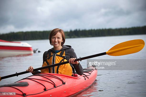 A woman wearing orange on a river in a red kayak