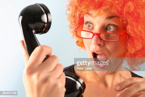 woman wearing orange wig looking at phone : Stock Photo