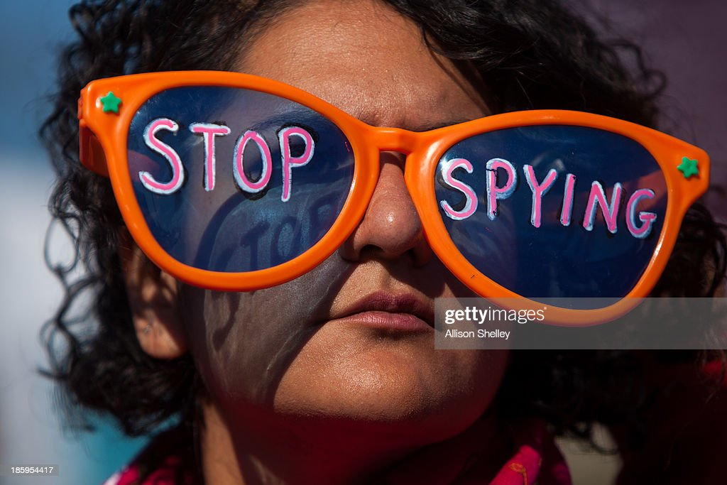 A woman wearing oversized sunglasses lettered with the words 'stop spying' listens to speakers during the Stop Watching Us Rally protesting...
