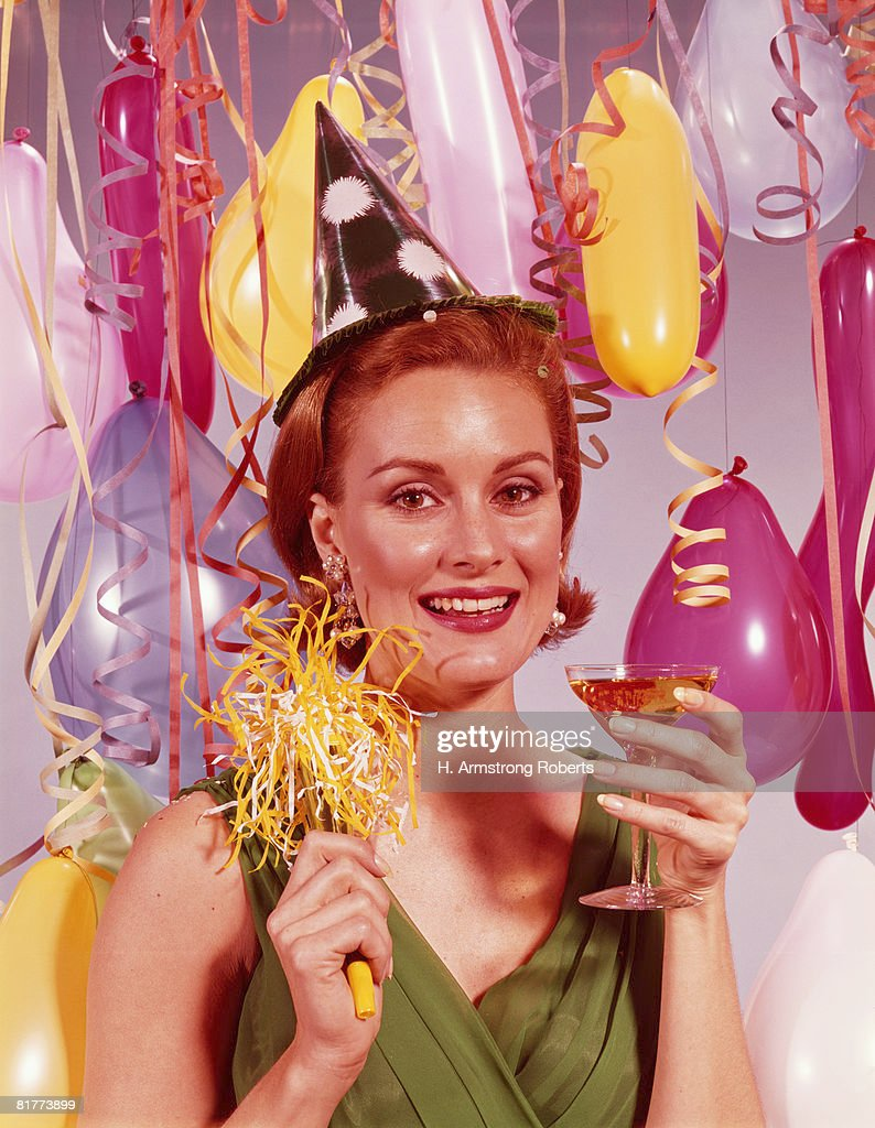 Woman wearing paper party hat, holding glass of champagne. (Photo by H. Armstrong Roberts/Retrofile/Getty Images) : Stock Photo