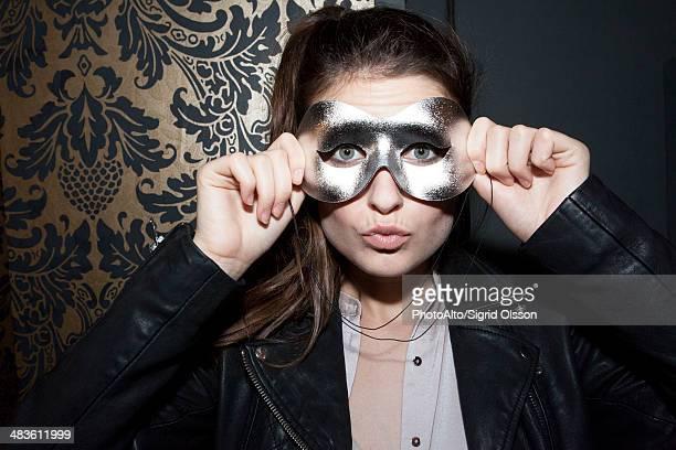 Woman wearing party mask, portrait