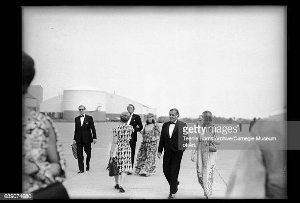 Woman wearing patterned suit walking out to greet other women and men from National Council on the Arts including Gregory Peck in center at airport...