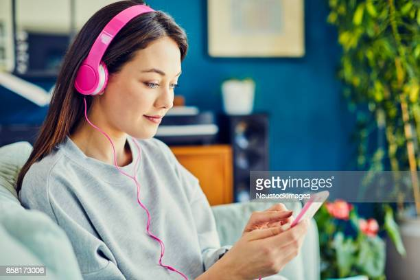 Woman wearing pink headphones while using smart phone at home