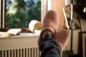Relaxing at home - woman wearing jeans and pink slippers taking a break and looking at beautiful day through sunny window at home
