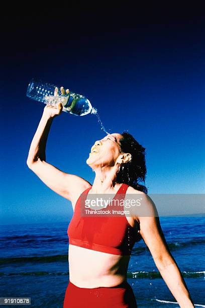 woman wearing  pouring bottled water on face,  sky and water in background