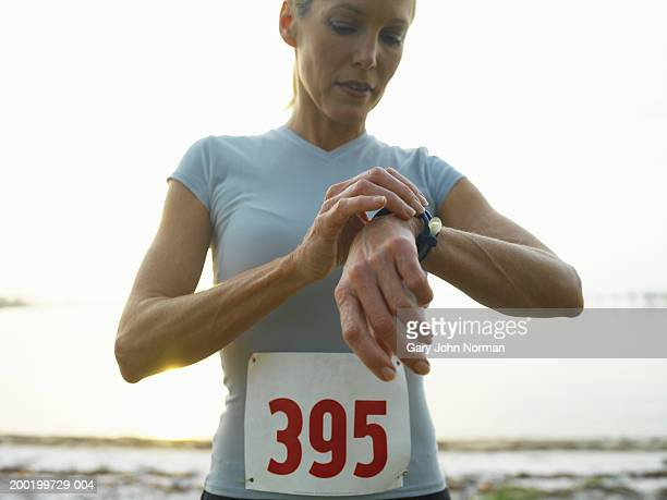 Woman wearing race number looking at watch, close-up