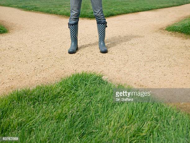 Woman wearing rainboots standing on dirt crossroad