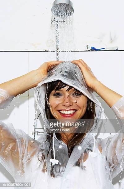 Femme portant manteau de pluie d'une douche séparée dans la salle de bains, souriant, portr