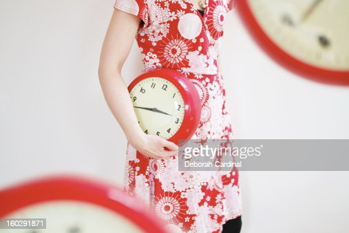 Woman wearing red dress holding a retro red clock : Stock Photo