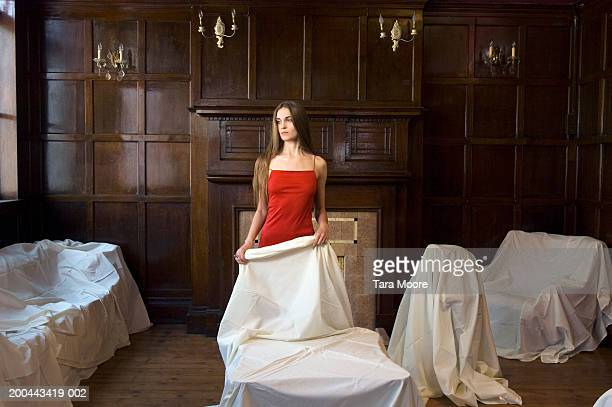 Woman wearing red dress holding dust sheet over furniture in room