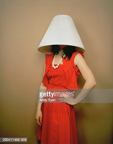 Woman wearing red dress with lamp shade on head and hand on hip