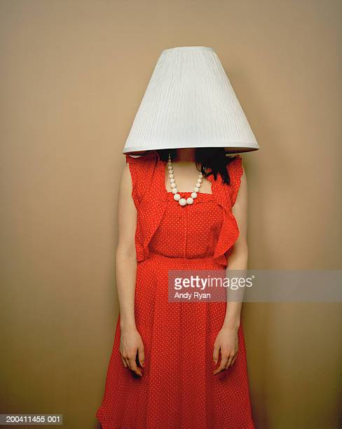 Woman wearing red dress with lamp shade on head