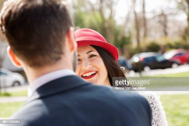Woman wearing red hat, smiles at boyfriend in city square.