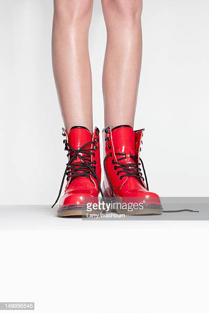 A woman wearing red patent leather boots, low section