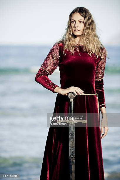 Woman wearing red velvet medieval gown holding a sword