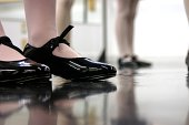 A group of girls in dance class - close up on the tap shoes and the reflections in the floor.