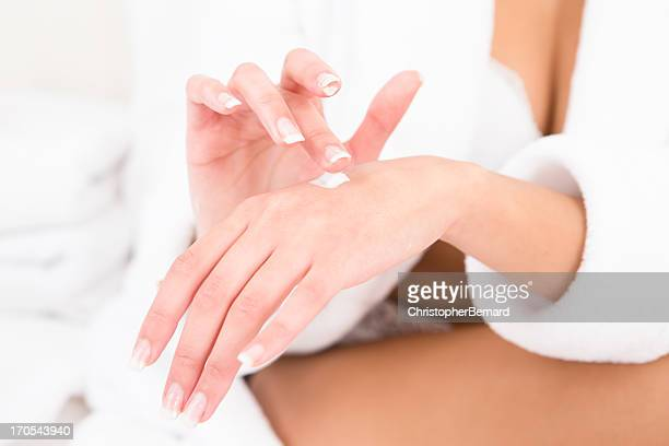 Woman wearing robe moisturizing hand