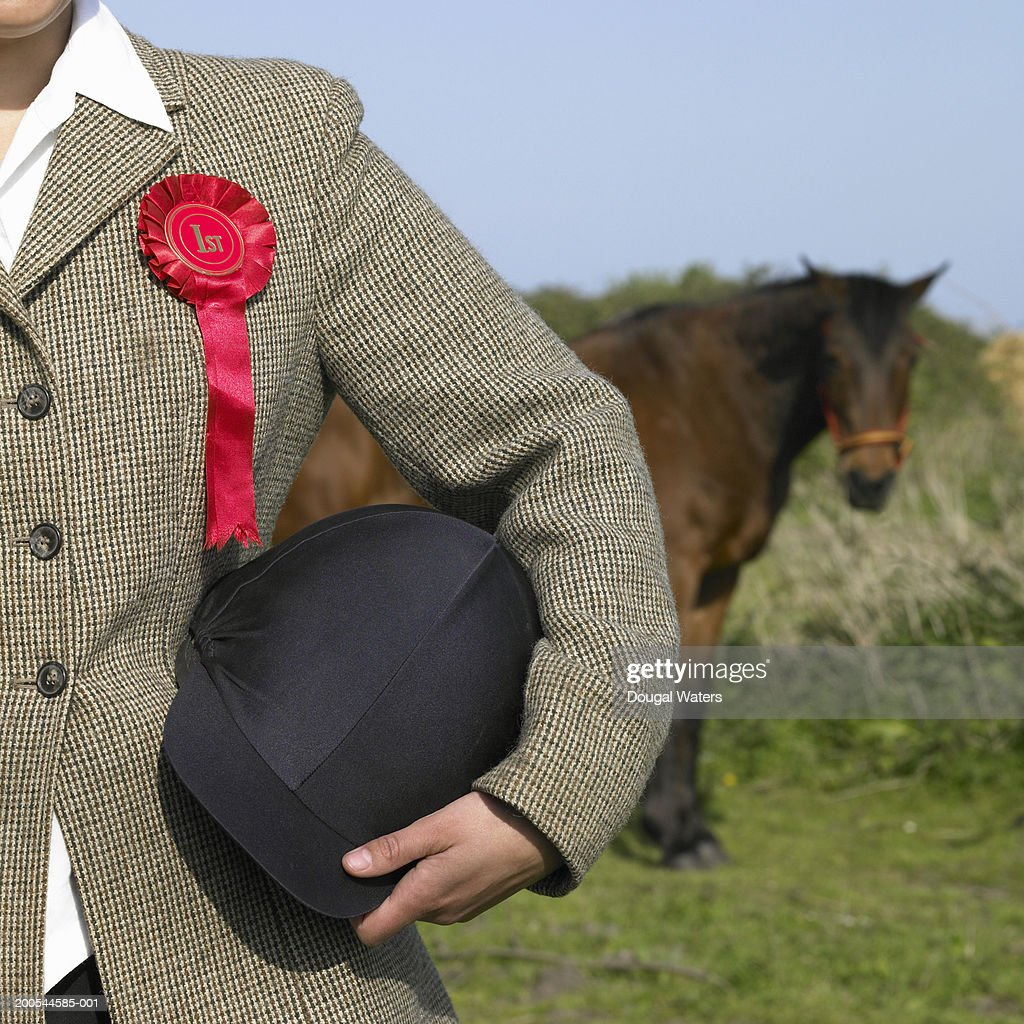 Woman wearing rosette wearing riding hat, close-up, mid section : Stock Photo