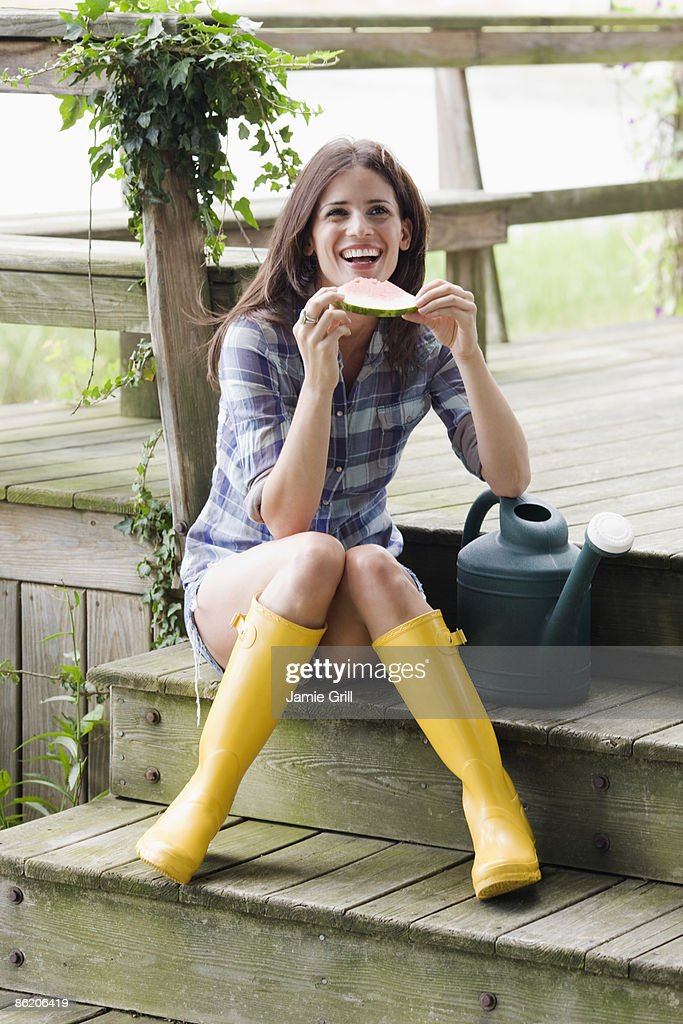 Woman Wearing Rubber Boots And Eating Watermelon On Deck