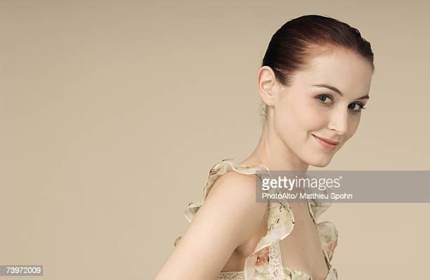 Woman wearing ruffled dress, hair in bun, smirking at camera, portrait