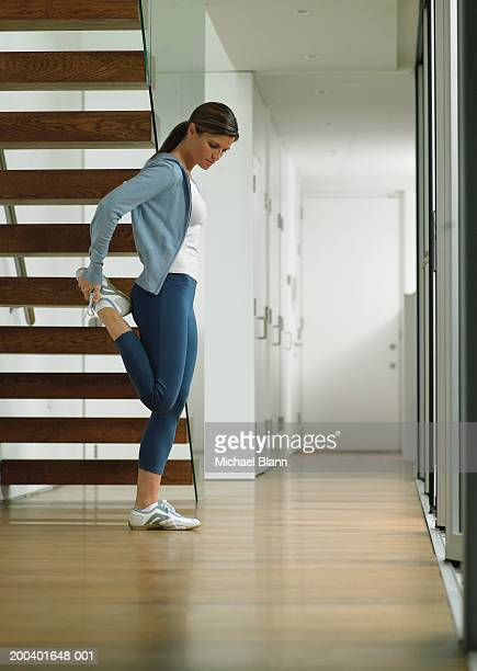 Woman wearing running clothes performing leg stretch by stairs