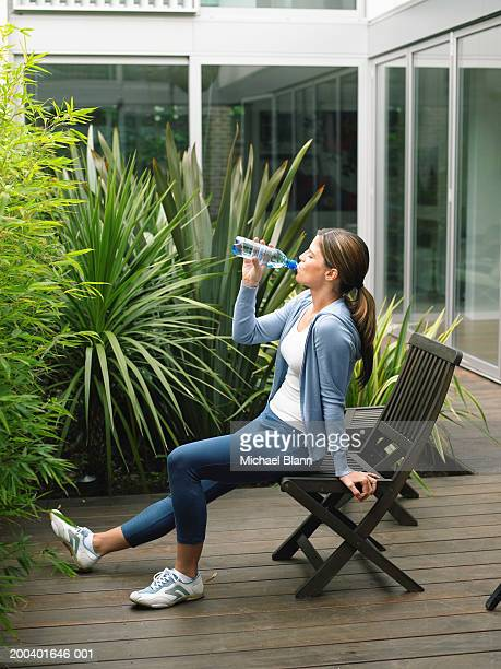 Woman wearing running clothes sitting on garden chair drinking water