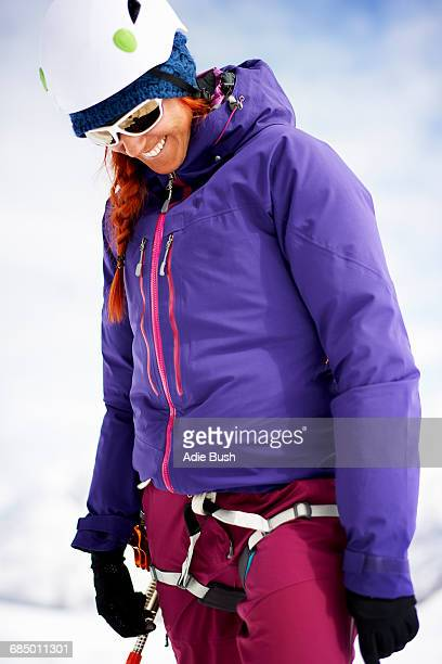 Woman wearing safety harness and climbing helmet looking down smiling
