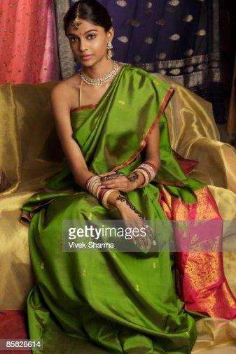 woman wearing sari, surrounded by sari fabric, decorated with henna tattoos, jewelry and bindi : Stock Photo