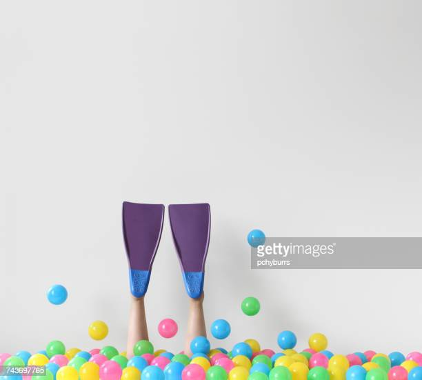 Woman wearing scuba fins diving into a conceptual ocean of plastic balls