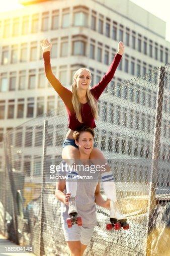 woman wearing skates on man's shoulders