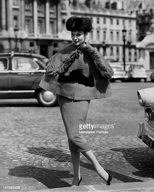 A woman wearing skirt and cape an ushanka and gloves of the French stylist Lanvin Castillo1956