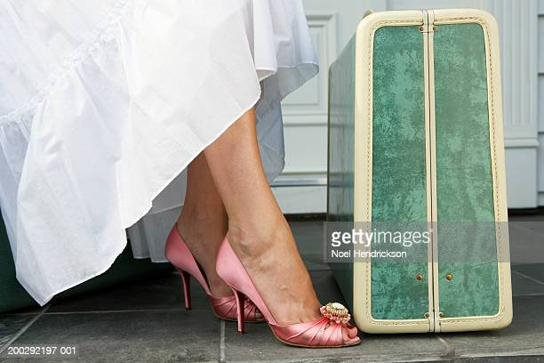 Woman wearing skirt and pink satin stilettos sitting beside suitcase, low section