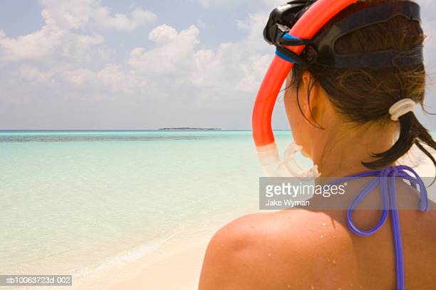 Woman wearing snorkelling gear at beach, rear view, close-up