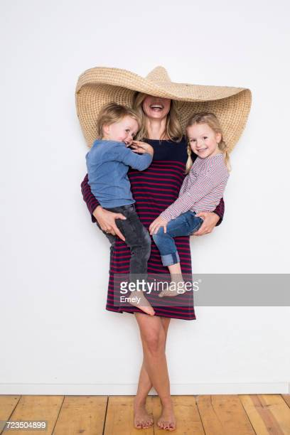 Woman wearing sombrero, shielding both herself and two children