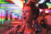 Young stylish woman wearing sparkling jacket on the city street with neon lights